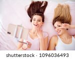 Small photo of Top view portrait of joyful, attractive girls with blonde, brunette hair laying on bed on back shooting selfie on front camera using smart phone, selfish stick, gesture peace symbol near eye