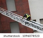 Small photo of One fireman walks on the long aerial ladder