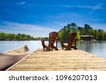 two muskoka chairs sitting on a ...   Shutterstock . vector #1096207013