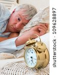 Ringing alarm clock and sleepy pensioner looking at it - stock photo
