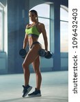Small photo of Athletic sporty woman posing with dumbbells in spacy gym with panoramic windows. Having strong, fit body with heatlthy tanned skin and muscles. Doing fitness exercises. Wearing modern sportswear.