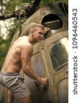 Small photo of Man climb on helicopter in forest. Sportsman with muscle body on heli aircraft. Travelling, discovery, adventure. Goal, achievement, success. Ambition, dream priority concept