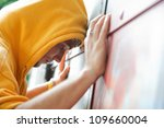 Young man in hooded sweatshirt / jumper facing grunge graffiti wall. Conceptual - stock photo