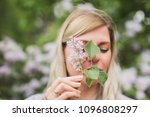 girl holding a sprig of lilac | Shutterstock . vector #1096808297