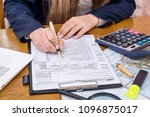 female hands filling 1040 form  ... | Shutterstock . vector #1096875017