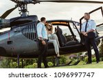 Small photo of Beautiful woman getting down the helicopter with the help from her boyfriend. Couple disembarking their helicopter with pilot standing by.