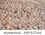 Small photo of Natural uncouth stone pavement texture background. Surface of the old cobblestone road.