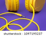 Small photo of Yellow jack plug cable and headphones on purple background. Music concept.