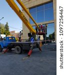 Small photo of Lutsk, Ukraine, May 23, 2018: Operator In Safety Helmet and red square shirt controlling Straight Boom Lift