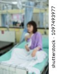 Small photo of Broken arm patient with arm sling for treatment in the hospital blurred.