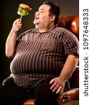 Small photo of Diet failure of fat man eating fast food hamberger. Happy smile overweight person who In business chair eating huge hamburger on fork. Junk meal leads to obesity. Feast on occasion of feast.