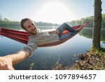 young man by the lake hanging... | Shutterstock . vector #1097894657