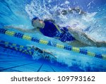 Low angle view of female swimmers gushing through water in pool - stock photo