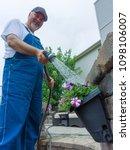 happy homeowner watering his... | Shutterstock . vector #1098106007