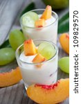Fresh peach and grape yogurt in glass - stock photo