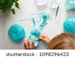 Small photo of Cute hand-knitted bunny, rabbit. On the table, knitting threads, knitting needles, a hook, ribbons. A little girl is learning to knit. Needlework. Flat lay.