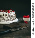 Small photo of Black Forest chocolate cake with fresh cherries and chocolates. with a knife all together on a wooden table top.