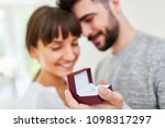 Small photo of Young man with wedding rings in a box makes a wife proposal to wife
