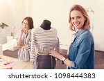 Small photo of Diligent worker. Smiling experienced designer standing near the mannequin and taking measurements while her colleague thinking about color patterns