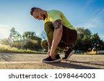 young handsome man tying shoe...   Shutterstock . vector #1098464003