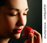 Face of attractive woman smelling strawberry with closed eyes - stock photo