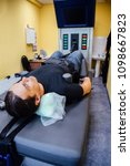 Small photo of Man at non-surgical spinal decompression procedure in medical center