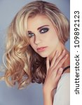 beautiful blond girl with curly long hair and smoky eyeshadow makeup - stock photo