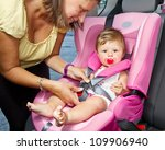 Woman fastening her son on a baby seat in a car - stock photo