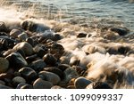 waves hit to the stones on the... | Shutterstock . vector #1099099337