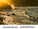stony beach with waves and with ... | Shutterstock . vector #1099099367