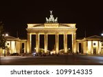 Brandenburg tor during night. Artist is playing with fire in front. - stock photo