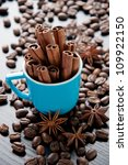 Vertical shot of espresso cup with cinnamon sticks, coffee beans and anise - stock photo
