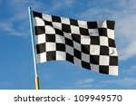 Checkered flag with blue sky on background - stock photo