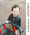 Small photo of Crying toddler stood holding on to swing in park.