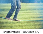 Small photo of Slackline. Close up on feet walking on tightrope outdoor in a city park