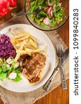 Small photo of Pork roulade with french fries with salad on a plate