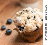 A Blueberry Muffin On A Wooden...