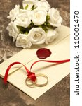 Wedding rings connected with red ribbon and invitation card - stock photo