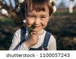 the small girl sniffs a flower | Shutterstock . vector #1100057243