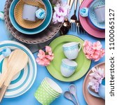 Small photo of Tableware dish set on blue pastel background with flowers. Flat lay