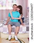 Small photo of As it is good to me with you. Portrait of a beautiful brunette girl sitting on the bed with a man. They sit right in front of the camera smiling and look happy