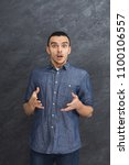 Small photo of Shocked man portrait. Young amazed guy looking at camera, gray studio background