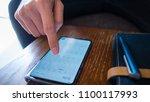 a man use smart phone show... | Shutterstock . vector #1100117993