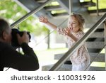 Father taking picture of smiling young girl outdoors - stock photo