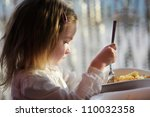 Cute little girl eating pasta outdoors - stock photo