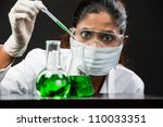 An Indian scientific researcher looking at a liquid solution. - stock photo