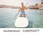 Small photo of Adult bearded man beginner surfer kneel on paddle board on sea. Summer active vacation and water sport concept