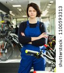 Small photo of Portrait of adult positive repairwoman standing near cycle in bicycle store