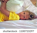 awaked boy lying in the bed on... | Shutterstock . vector #1100723297