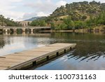 A pier floating on the water of a river with a bridge and a dam in background in a cloudy day